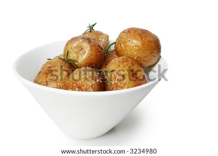 Salt roasted baby potatoes with rosemary, in a white bowl. - stock photo