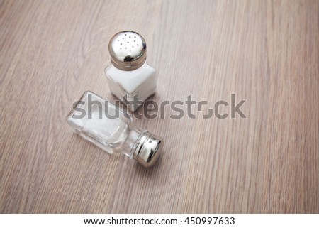 Salt shaker with salt and white pepper on the empty wooden kitchen table - stock photo
