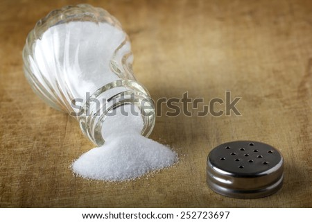 Salt sprinkled on a wooden table - stock photo
