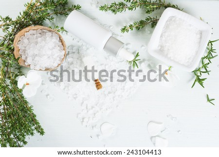 salt with flowers and savory twigs on white wood table - stock photo