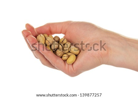 Salted and roasted pistachio nuts in a hand, isolated on white - stock photo