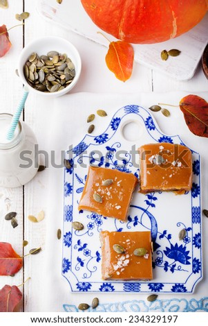 Salted caramel with pumpkin puree and  seeds on a blue and white ceramic board. - stock photo