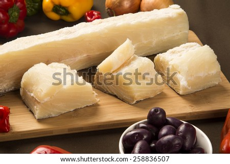 salted codfish on the wooden table with ingredients - stock photo