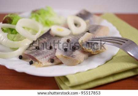 salted herring on a plate on a wooden table - stock photo
