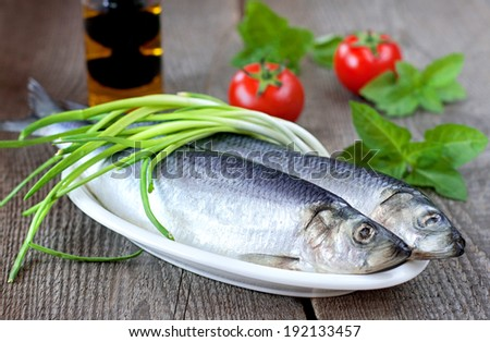 Salted herring on a wooden table with green onion, tomatoes, green basil and olive oil - stock photo