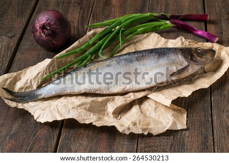 Salted herring, red and green onions on wrapping paper and wooden background. Selective focus - stock photo