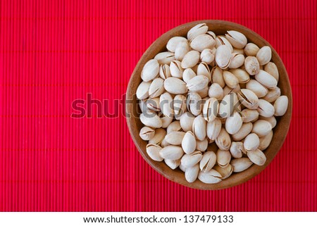 Salted peanuts in wooden bowl on red bamboo tablecloth. - stock photo