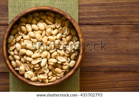 Salted peanuts in wooden bowl, photographed overhead on dark wood with natural light (Selective Focus, Focus on the top peanuts) - stock photo