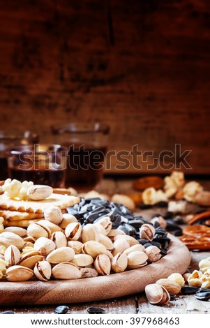 Salted pistachios, popcorn and other salty snacks on a wooden platter, selective focus - stock photo