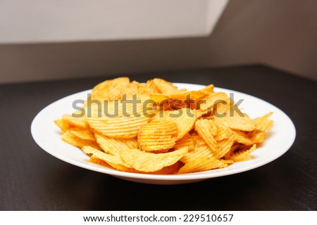 Salted potato chips served in a white bowl - stock photo