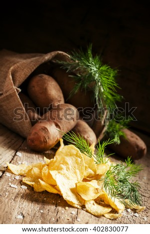 Salted potato chips with herbs on a wooden table vintage, country style, selective focus - stock photo