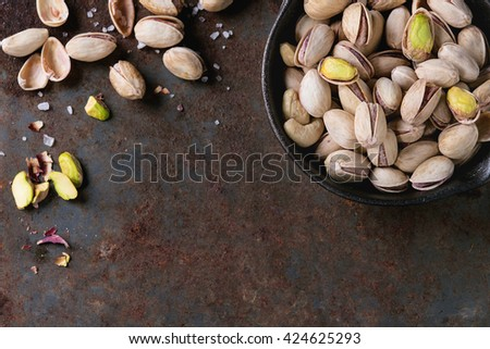 Salted roasted pistachios nuts with shell and salt  in  in black small cast-iron pan over old rusty iron textured background. Top view. With copy space - stock photo