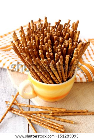 salted sticks in yellow cup on wooden - stock photo