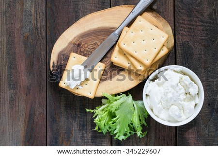 Saltine crackers on a wooden board, lettuce, ricotta in a jar, topped with a knife on a cracker - stock photo