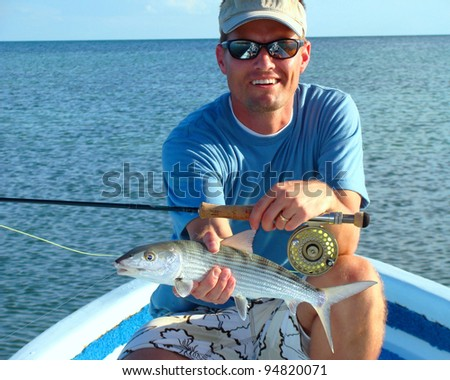 Saltwater Fly Fisherman with the elusive bonefish, fly rod and reel - stock photo