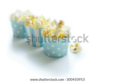 Salty caramel popcorn in baby blue containers isolated on white. Delicious party snack. Natural back light, shallow depth of field. - stock photo