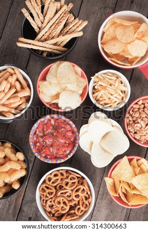 Salty crackers, tortilla chips and other savory snacks with salsa dip - stock photo