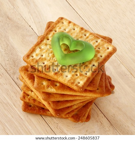 Salty Crackers with green heart are on wooden background. - stock photo