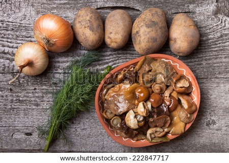 Salty mushrooms, potato, onion, dill and grain in a bowl on a old wooden board - stock photo