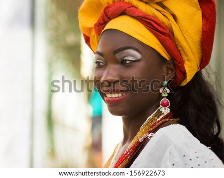 SALVADOR, BAHIA, BRAZIL - OCTOBER 13th, 2012: A Brazilian woman of African descent, smiling, wearing traditional clothes from the state of Bahia in the old colonial district of Salvador (Pelourinho). - stock photo