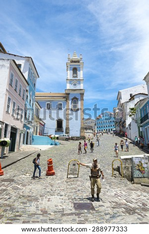 SALVADOR, BRAZIL - MARCH 12, 2015: Brazilian policeman directs traffic in front of colorful colonial architecture on a broad cobblestone hill in the historic city center of Pelourinho.  - stock photo