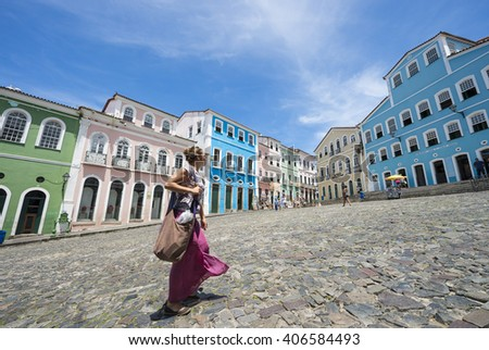 SALVADOR, BRAZIL - MARCH 12, 2015: Pedestrian passes in front of colorful colonial architecture on a broad cobblestone hill in the historic city center of Pelourinho.  - stock photo