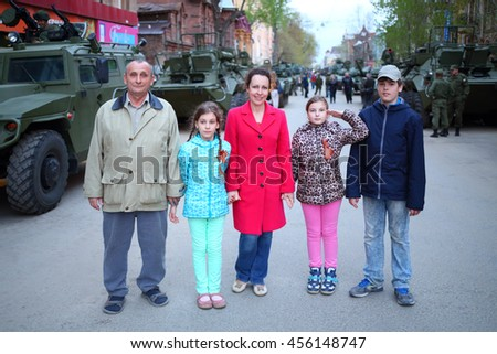 SAMARA - MAY, 6, 2015: Boy, man, woman and two girls (with model releases) pose near armored vehicles during military celebration. Red Square is not affected by military equipment on parade May 9th - stock photo