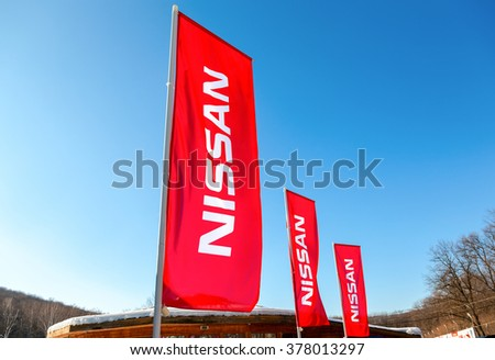 SAMARA, RUSSIA - FEBRUARY 14, 2016: Dealership flags Nissan over blue sky in sunny day. Nissan is a Japanese multinational automaker - stock photo