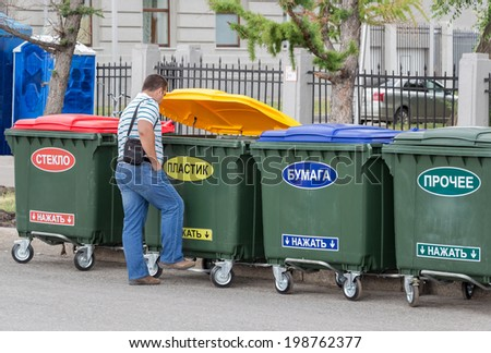 """SAMARA, RUSSIA - JUNE 12, 2014: Man throws trash in the dumpster with inscription on russian: """" Plastic"""" - stock photo"""
