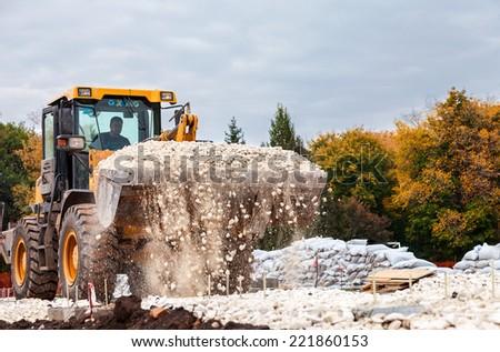 SAMARA, RUSSIA - SEPTEMBER 28, 2014: Heavy bulldozer loading and moving gravel on road construction site - stock photo
