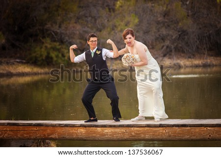 Same sex female couple having fun on dock near lake - stock photo
