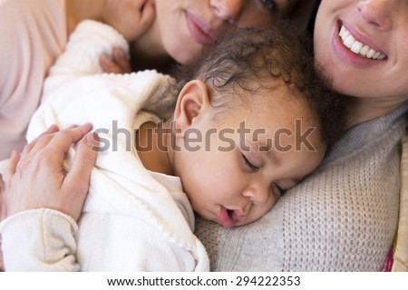 Same sex female couple lying down with their baby son - stock photo