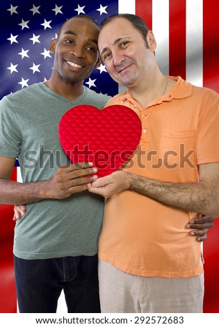 Same sex gay couple legally married in United States of America.  The interracial couple has an American flag in the background. - stock photo