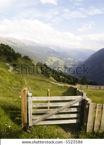 Samll wooden gate. In background view on austrian Alps. - stock photo