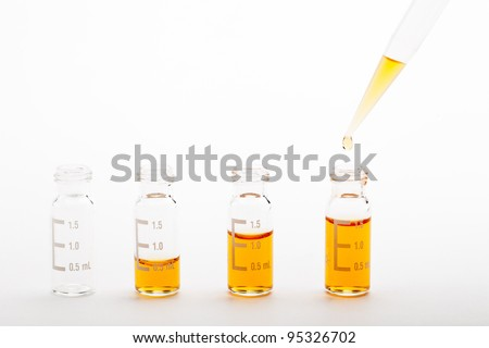Sample preparation. Chromatographic glass vials filled with different volumes of orange liquid and a pipette tip with a droplet. Clipping path included. See my portfolio for similar images - stock photo
