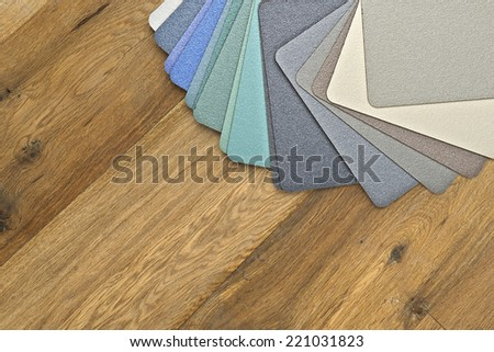 Samples of collection textured and colored fabrics on wooden floor - stock photo