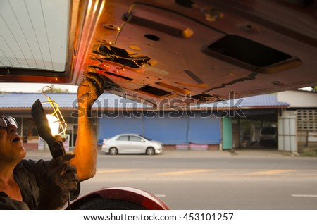 SAMUT SAKHON, THAILAND - MAY 19 : Old man 60 year old thai people professional automotive motor use lighting lamp for repair back door of car at local shop on May 19, 2016 in Samut Sakhon, Thailand - stock photo