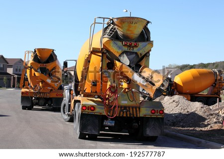 SAN ANTONIO, TX - OCTOBER 21, 2011 : Concrete mixing trucks create a traffic jam in a residential street as new home construction picks up - stock photo