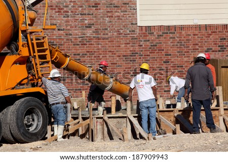 SAN ANTONIO, TX - OCTOBER 21, 2011: Workers pour concrete for a house foundation as new home construction picks up - stock photo
