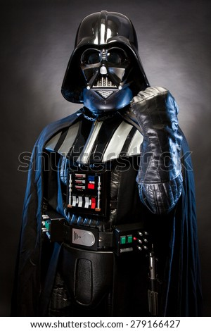 SAN BENEDETTO DEL TRONTO, ITALY. MAY 16, 2015. Half-lenght portrait of Darth Vader with fist punch . Darth Vader is a fictional character of Star Wars saga. Black background. Blue grazing light - stock photo