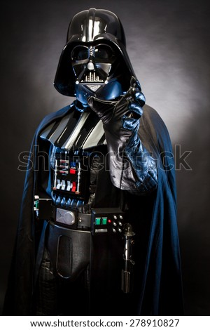 SAN BENEDETTO DEL TRONTO, ITALY. MAY 16, 2015.  Half-lenght portrait of Darth Vader with grab hand . Darth Vader is a fictional character of Star Wars saga. Black background. Blue grazing light - stock photo