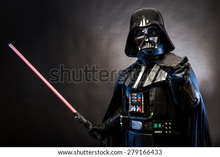 SAN BENEDETTO DEL TRONTO, ITALY. MAY 16, 2015. Portrait of Darth Vader costume replica with grab hand and his sword . Darth Vader is a fictional character of Star Wars saga. Black background.  - stock photo