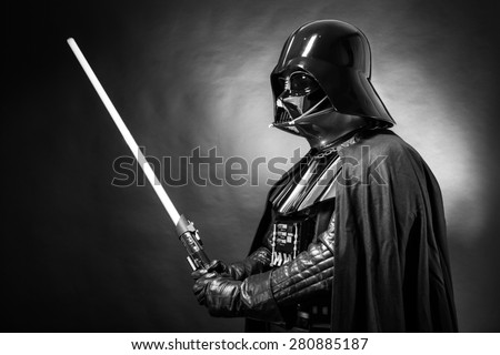 SAN BENEDETTO DEL TRONTO, ITALY. MAY 16, 2015. Portrait of Darth Vader costume replica with his sword . Darth Vader is a fictional character of Star Wars saga. Black and white pictures. - stock photo