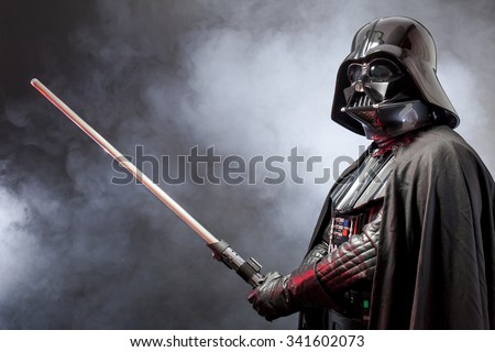 SAN BENEDETTO DEL TRONTO, ITALY. MAY 16, 2015. Portrait of Darth Vader costume replica with his sword . Lord Fener is a fictional character of Star Wars saga.  Black background with smoke - stock photo