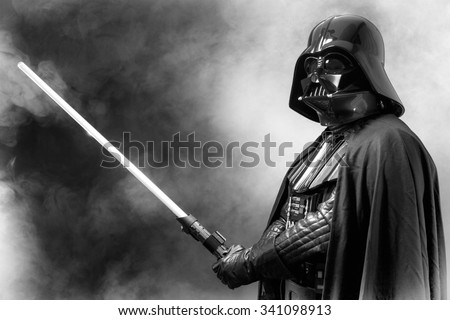 SAN BENEDETTO DEL TRONTO, ITALY. MAY 16, 2015. Portrait of Darth Vader costume replica with  sword . Lord Fener is a fictional character of Star Wars saga.  Black and white picture, smoke background - stock photo