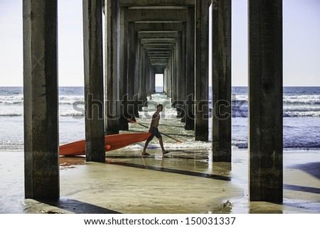 SAN DIEGO, CALIFORNIA - MARCH 31: Unidentified man dragging a canoe boat walking through the Scripps Pier on March 31, 2013 in La Jolla, San Diego, CA, USA.  La Jolla Shore is a popular launch point for canoeing. - stock photo