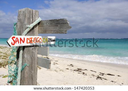 San Diego direction and distance signpost on a beach in Governor's Harbour, Eleuthera, Bahamas, Caribbean - stock photo