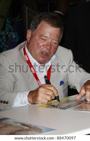 SAN DIEGO - JULY 23: William Shatner signs autographs during Day 2 of Comic-Con 2010 in San Diego, California on July 23, 2010 - stock photo