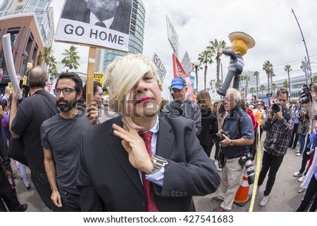 SAN DIEGO, USA - MAY 27, 2016: An anti-Trump protester personifies Donald Trump by wearing a blonde wig amidst a crowd of demonstrators outside at Trump rally at the San Diego Convention Center - stock photo