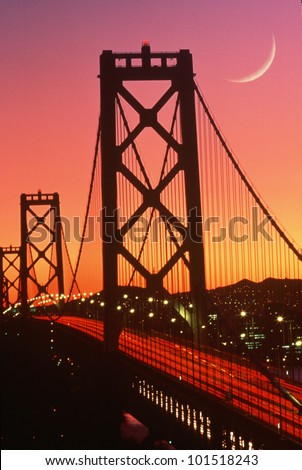 San Francisco Bay Bridge with crescent moon at sunset - stock photo